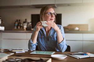 mulher sentada à mesa com xícara de café nas mãos