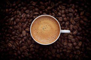 xícara de café vista de cima envolta de grãos