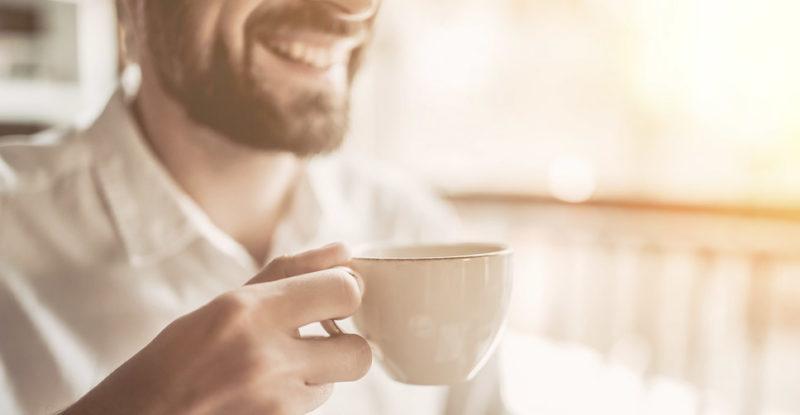 homem sorrindo com xícara de café na mão
