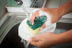 Esponja com sabão lavando prato durante o processo de como higienizar pratos e talheres