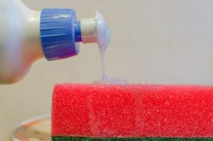 Um dos produtos de limpeza concentrados é despejado sobre uma esponja vermelha