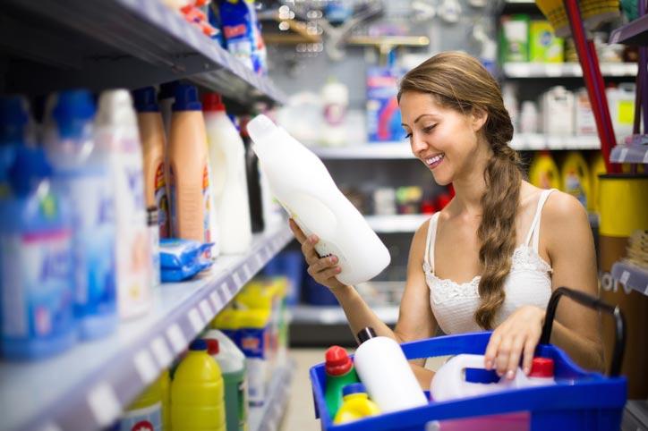 Escolher desinfetante: mulher no supermercado com uma cesta de produtos de limpeza na mão, sorrindo para uma das embalagens