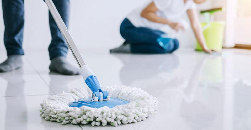 Pessoa utilizando a vassoura certa em um piso branco de aspecto liso
