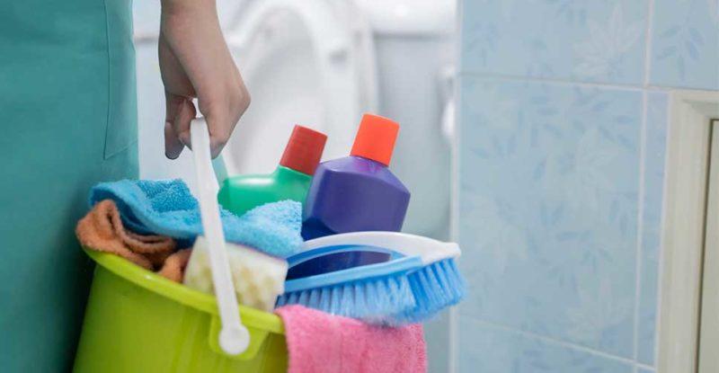 Mulher segurando um balde com vários produtos de limpeza. Dentre eles estão os tipos de detergente.
