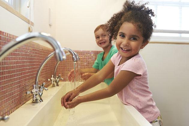 crianças lavando as mãos no banheiro da escola