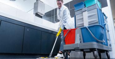 Mulher limpando o banheiro da empresa de luvas amarelas