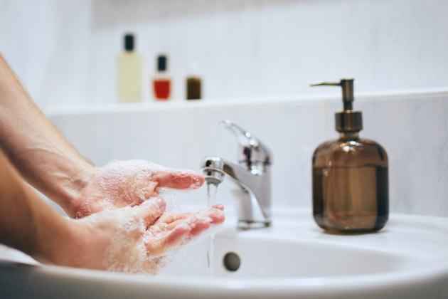 Pessoa lavando as mãos com sabonete líquido que é um dos tipos de sabão