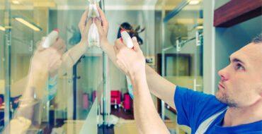 Homem branco que conhece como limpar vidros da empresa realizando a higienização