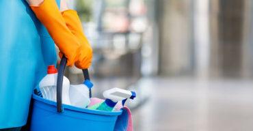 Profissional segurando um balde com produtos utilizados para higienização hospitalar