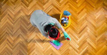 Profissional higienizando o chão. Veja como economizar com soluções caseiras para limpeza de pisos!