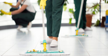 três profissionais da área de limpeza com rodos no chão realizam a limpeza estratégica para condomínio